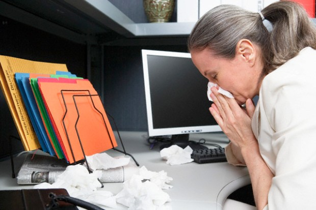 Businesswoman Blowing Nose at Desk