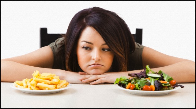 Young woman choosing between healthy and unhealthy food